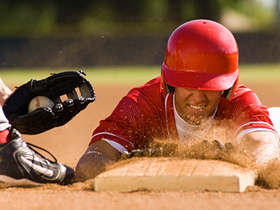 Baseball player sliding into base.