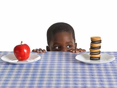 Boy looking at apple and cookies on table.