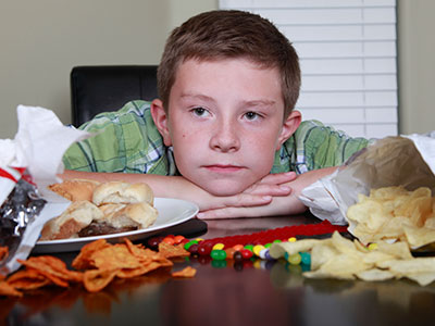 Boy sitting at table piled with junk food.
