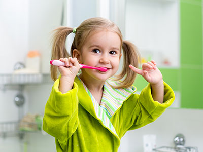 Little blond girl brushing teeth.