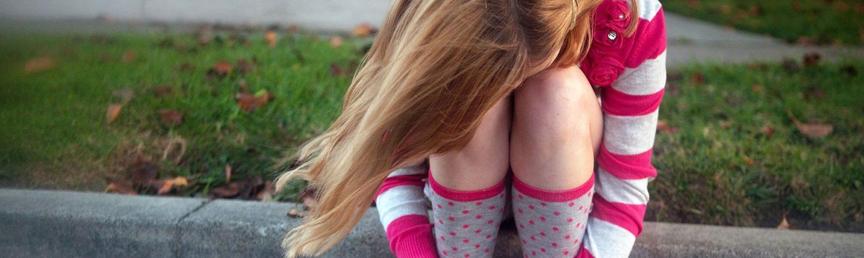 Sad girl in striped shirt sitting on a curb.