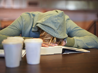 Teen siting at desk asleep on a book.
