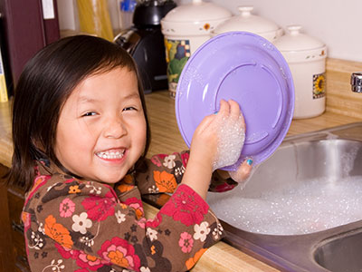 Little girl washing dishes.