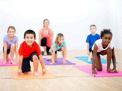Kids doing yoga in a gym