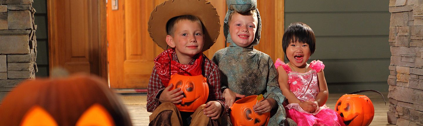 Kids in Halloween costumes sitting in front of a house