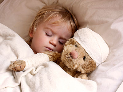 Little boy asleep in bed with teddybear