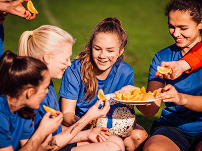 girls soccer team eating oranges