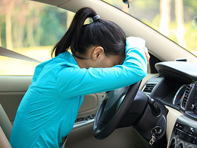 girl leaning against steering wheel in car