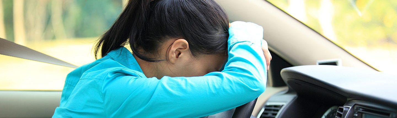 girl leaning against steering wheel in car