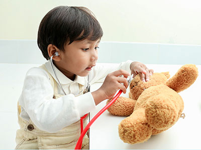 little boy listening to teddy bear's heart with stethoscope