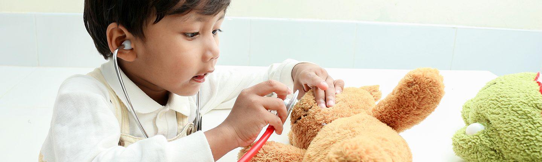 little boy listening to teddy bear's heart with stethoscope