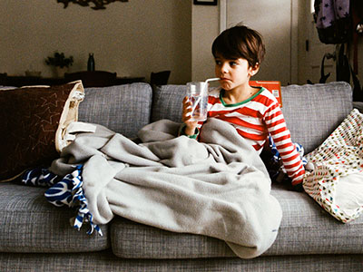 little boy sitting on couch drinking from a straw-featured