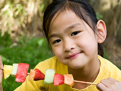 little girl eating fruit kabob