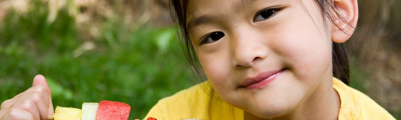 little girl eating fruit kabob