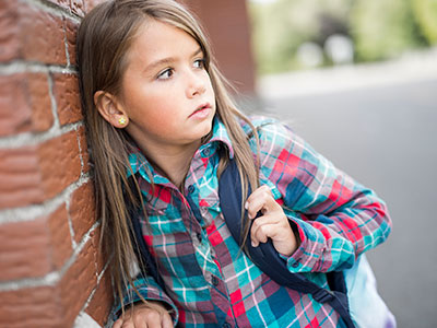 little girl leaning against wall