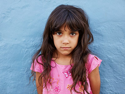 little girl standing against blue wall