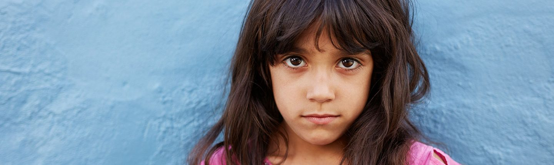little girl standing against blue wall