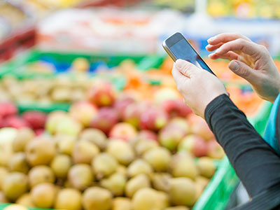 Person in produce aisle with smartphone