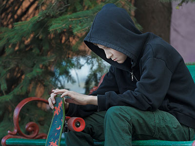 sad teenager looking at skateboard in his hands