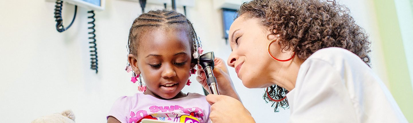 doctor marcee white examines a little girl's ears