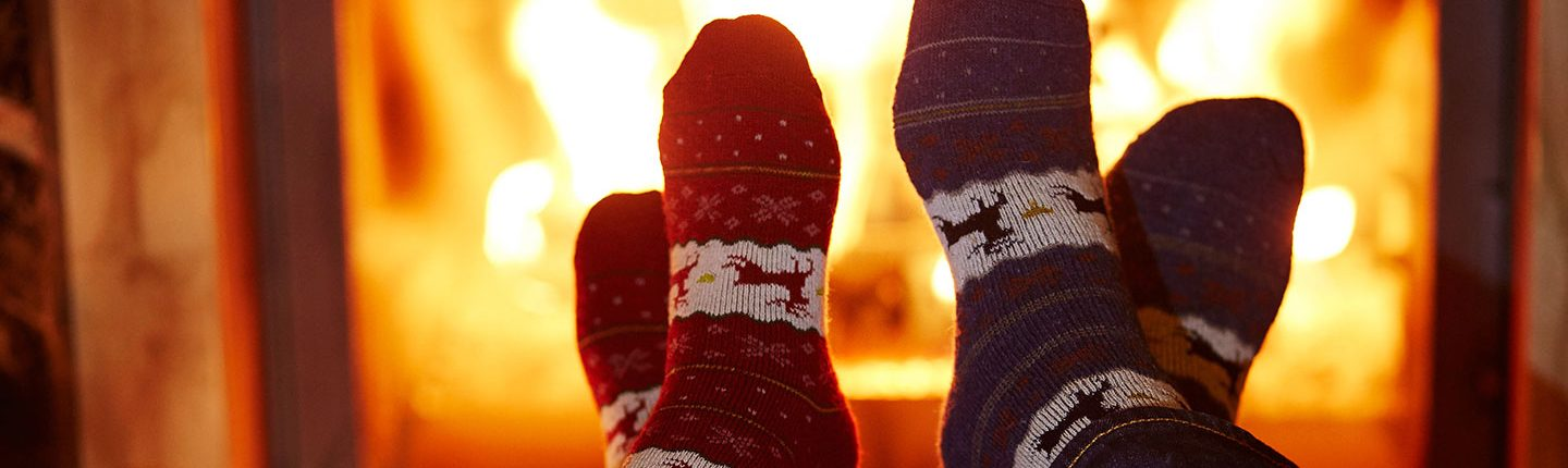 Man and woman in warm socks near fireplace