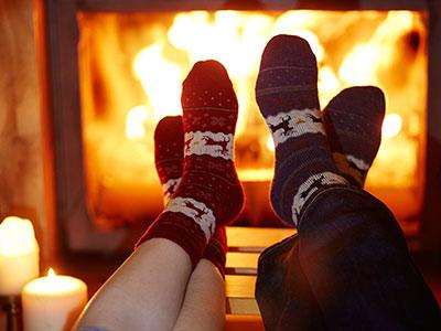 Man and woman in warm socks near fireplace
