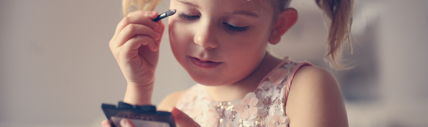 Little girl putting on makeup