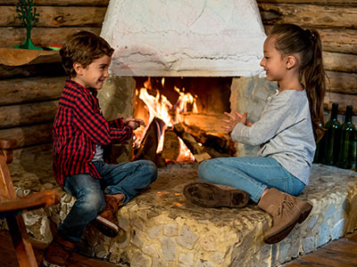 boy and girl sitting by fireplace