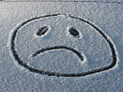 frowny face drawn in the snow