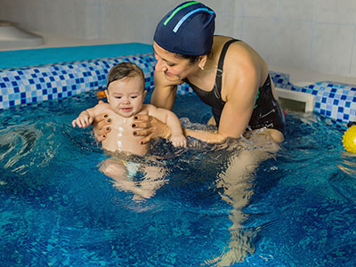 woman teaching baby to swim