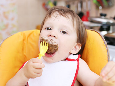 baby eating hamburger meat