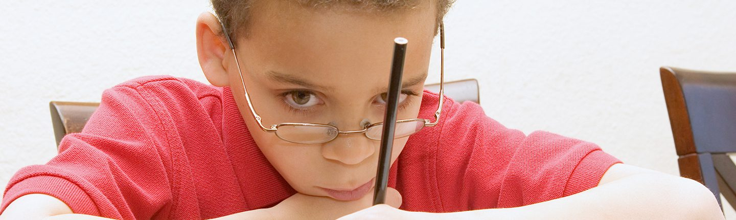 sad looking kid with pencil
