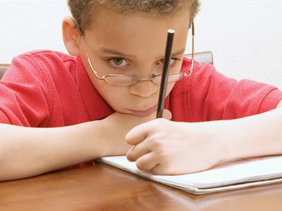 sad looking kid with pencil
