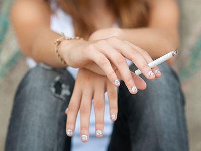 teeaged girl holding a cigarette