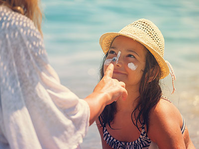 mother applying sunscreen to daughter's face