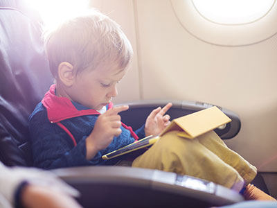 little boy using tablet on plane