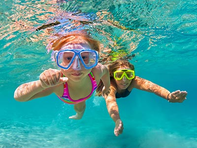mother and daughter swimming underwater