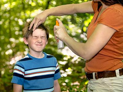 Mother Applying Bug Spray to son