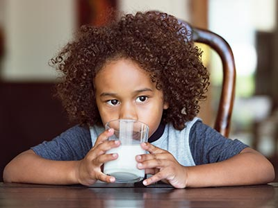 Thoughtful boy drinking milk at home
