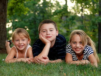 three kids lying in the grass
