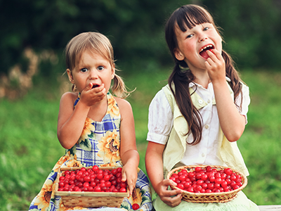 two girls eating cherries