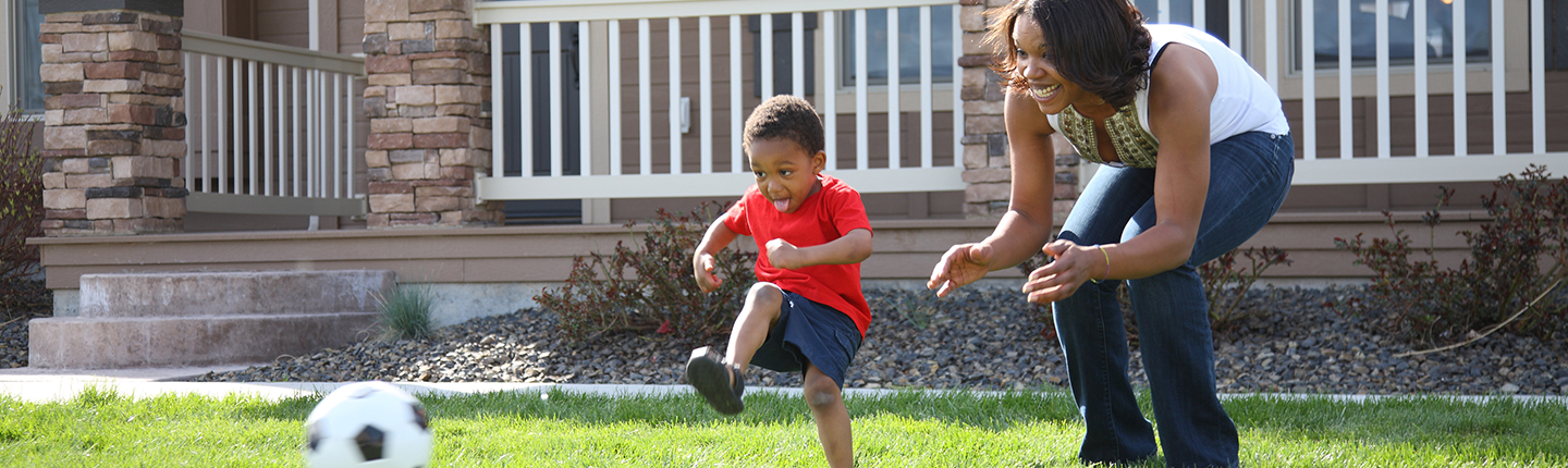 Little boy kicking soccer ball with mom