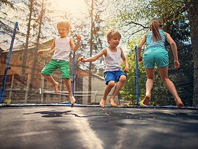 Three kids jumping on large trampoline