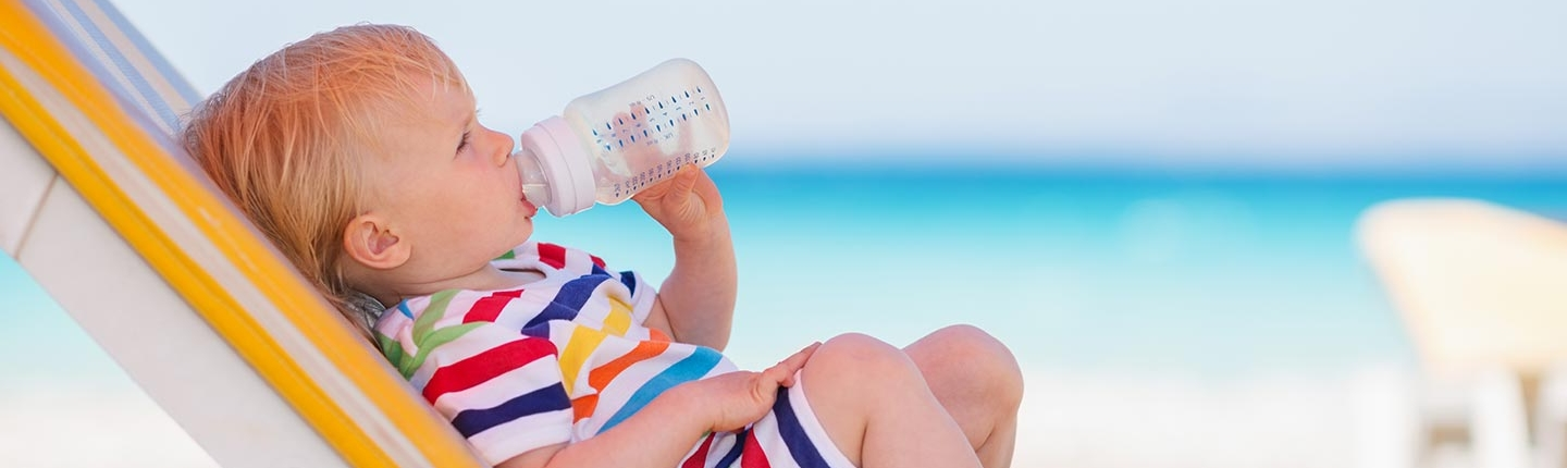 baby drinking from bottle on the beach