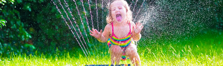 little girl playing in sprinkler
