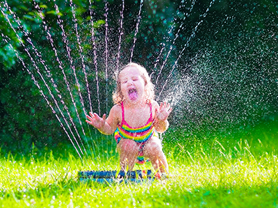 little girl playing in sprinkler