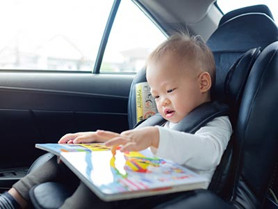 toddler boy sitting in car seat reading book