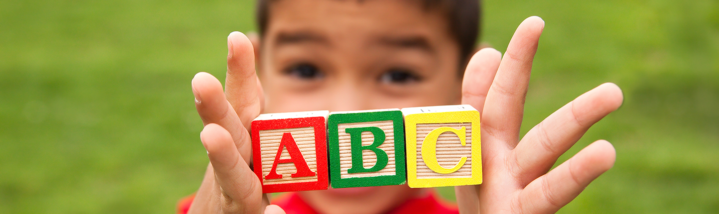 Little boy holding ABC blocks