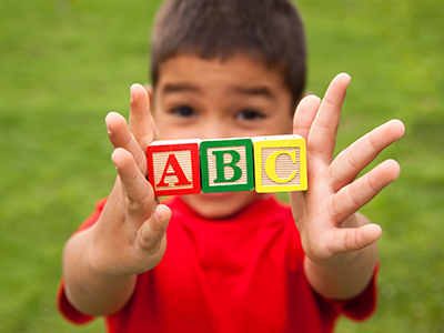 School kid holding abc blocks
