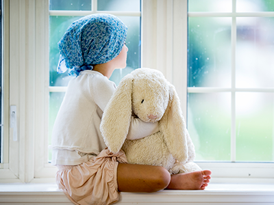 girl with stuffed rabbit looking out window
